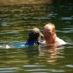 Dad and son swimming at a lake